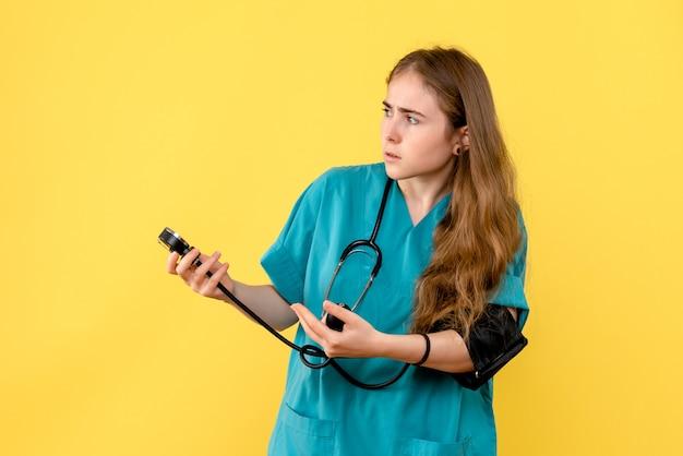 Médica de frente medindo a pressão no fundo amarelo.