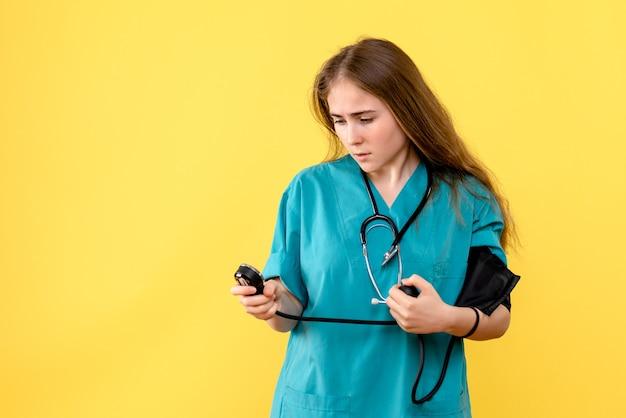 Médica de frente medindo pressão sobre fundo amarelo hospital médico