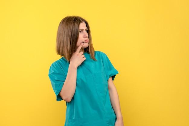 Médica de frente no espaço amarelo