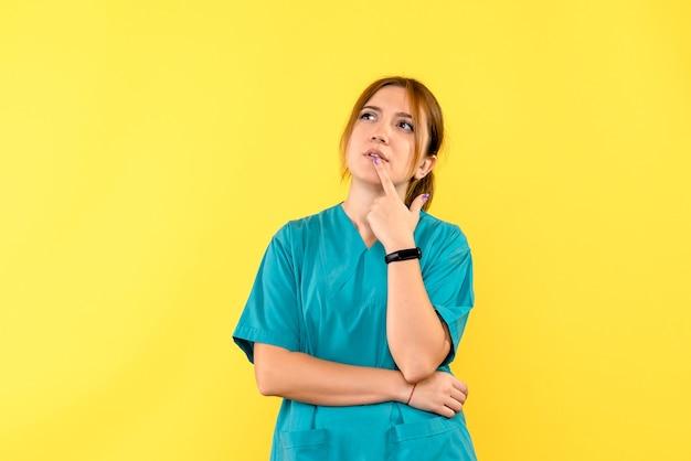 Médica de frente pensando no espaço amarelo