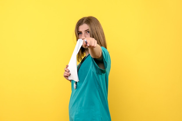 Médica de frente segurando arquivos no espaço amarelo
