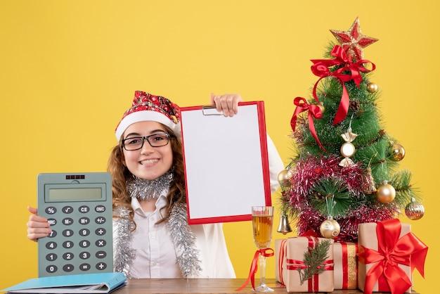 Médica de frente segurando calculadora e nota de arquivo