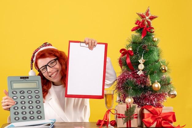 Médica de frente segurando calculadora em volta dos presentes de natal e árvore