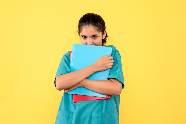 Médica de frente segurando documentos