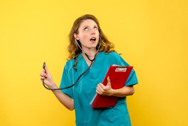 Médica de frente segurando o estetoscópio no espaço amarelo