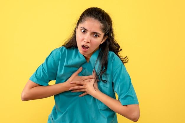 Médica de frente segurando o peito em pé