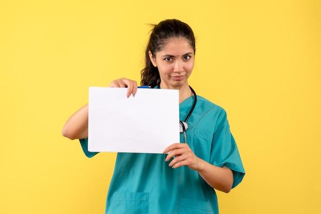 Médica de frente segurando papéis em pé