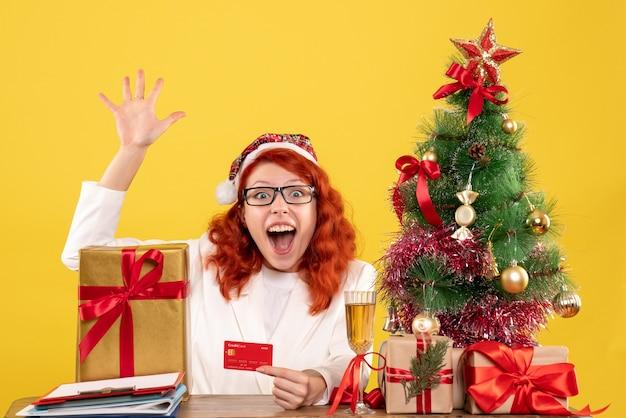 Médica de frente segurando um cartão do banco em torno de presentes de natal e árvore