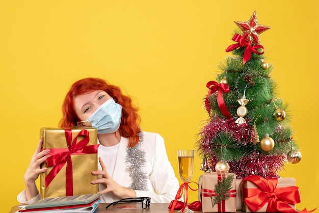 Médica de frente segurando um presente