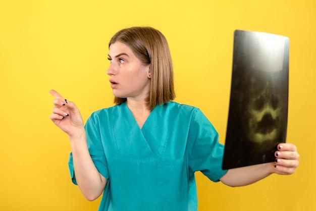 Médica de frente segurando um raio-x no espaço amarelo
