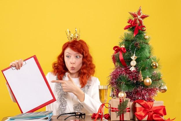 Médica de frente segurando uma nota de arquivo ao redor da árvore de natal e presentes