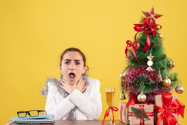 Médica de frente, sentada atrás da mesa, com problemas de garganta em fundo amarelo, com árvore de natal e caixas de presente
