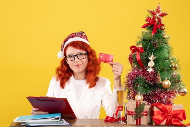 Médica de frente, sentada atrás da mesa, segurando o cartão do banco em fundo amarelo com árvore de natal e caixas de presente
