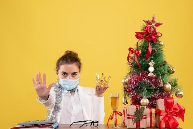 Médica de frente sentada com máscara estéril segurando uma coroa sobre fundo amarelo com árvore de natal e caixas de presente