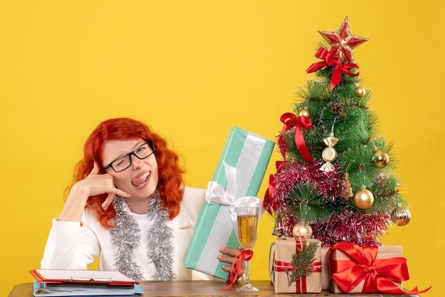 Médica de frente sentada com os presentes de natal e a árvore na mesa amarela