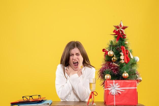 Médica de frente, sentada em frente à mesa, com dor de garganta em fundo amarelo, com árvore de natal e caixas de presente