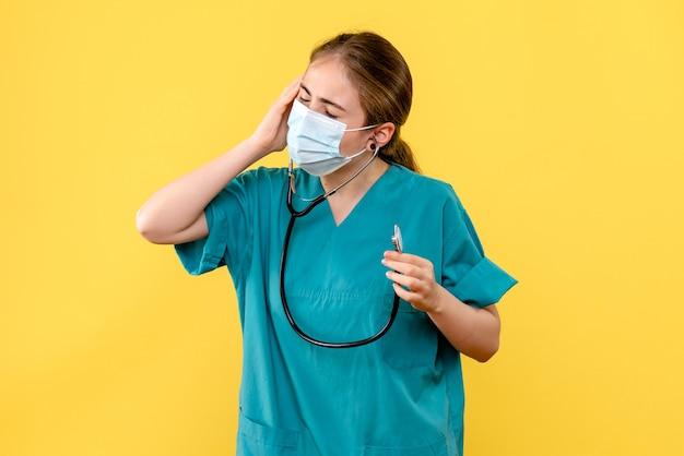 Médica de frente, tendo dor de cabeça na máscara sobre fundo amarelo, vírus da saúde pandêmico covid