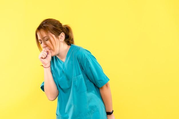 Médica de frente tossindo no espaço amarelo