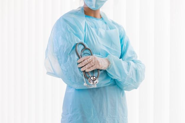 Médica de frente usando roupas de proteção