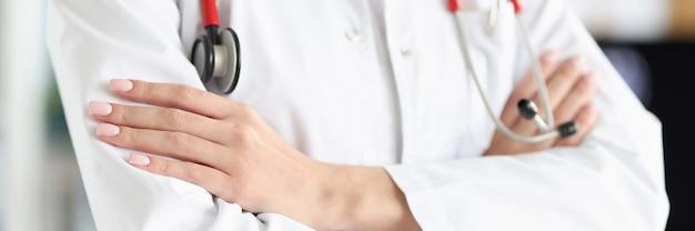 Médica de jaleco branco e estetoscópio em pé com os braços cruzados