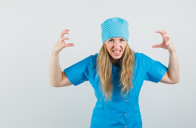Médica de mãos dadas de maneira agressiva em uniforme azul e parecendo furiosa