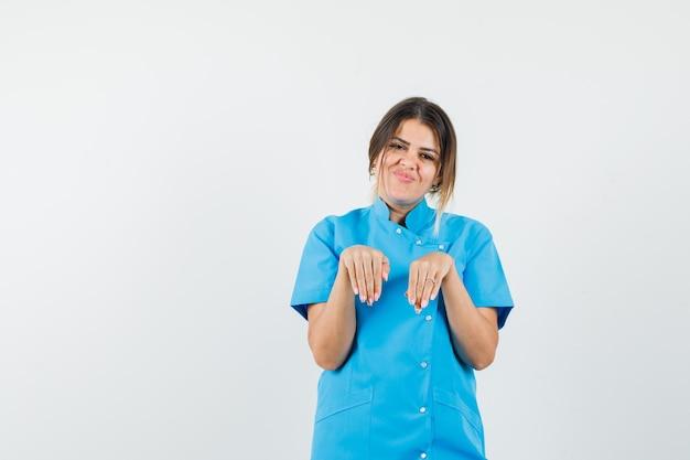 Médica de mãos dadas em um gesto engraçado em uniforme azul e parecendo alegre