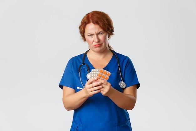 Médica de meia-idade, careta decepcionada, segurando um medicamento ruim, mostrando pílulas horríveis, não recomendo este vitaminas ou comprimidos