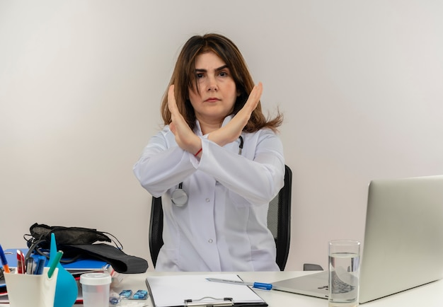 Médica de meia-idade, carrancuda, vestindo túnica médica e estetoscópio sentada à mesa com a área de transferência de ferramentas médicas e laptop sem fazer nenhum gesto isolado
