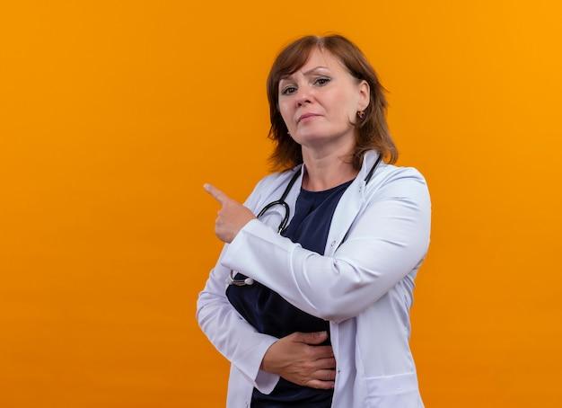 Médica de meia-idade com aparência séria, vestindo bata médica e estetoscópio apontando com o dedo para o lado esquerdo em uma parede laranja isolada com espaço de cópia