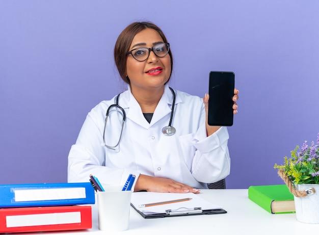 Médica de meia-idade com jaleco branco com estetoscópio e óculos, mostrando o smartphone, sorrindo confiante, sentado à mesa sobre a parede azul
