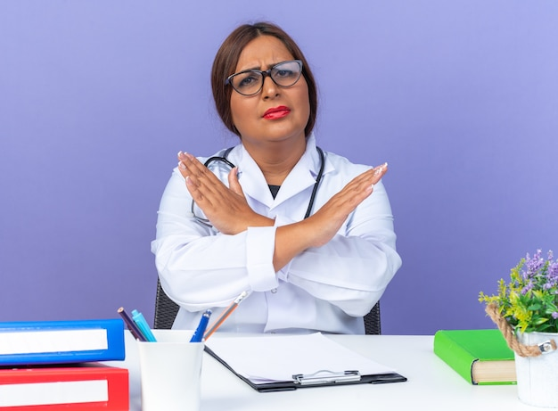 Médica de meia-idade com jaleco branco com estetoscópio e óculos, olhando para a frente com uma cara séria, fazendo gesto de parada, cruzando as mãos, sentado à mesa sobre a parede azul