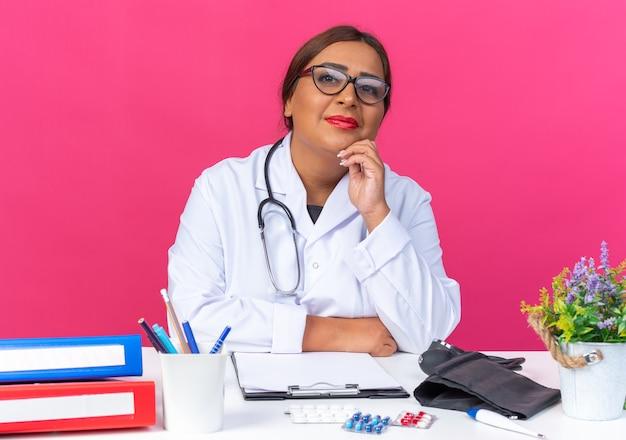 Médica de meia-idade com jaleco branco com estetoscópio e óculos, olhando para a frente, sorrindo confiante, sentado à mesa sobre a parede rosa