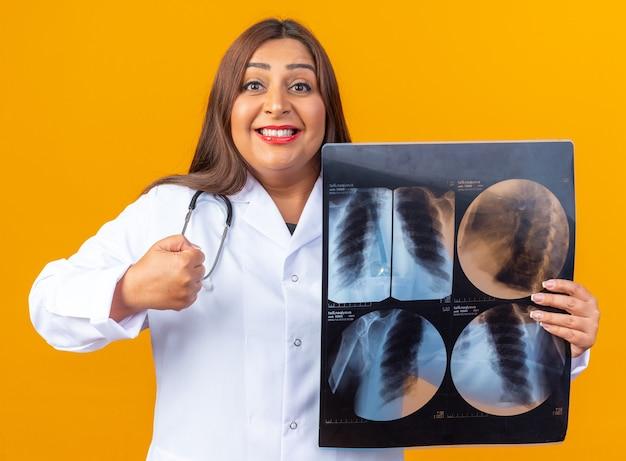 Médica de meia-idade com jaleco branco com estetoscópio segurando um raio-x feliz e positiva com o punho cerrado