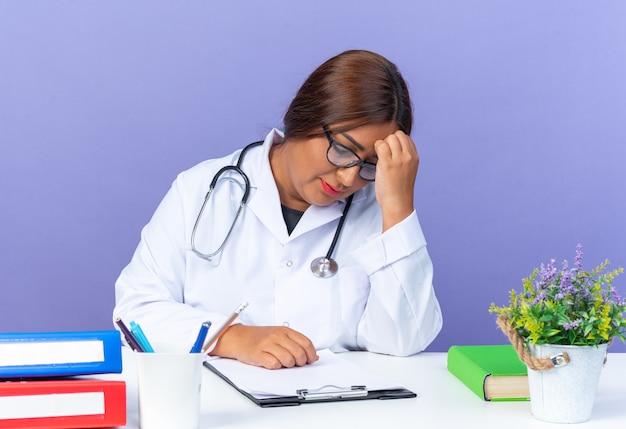 Médica de meia-idade com jaleco branco e estetoscópio parecendo cansada e sobrecarregada, sentada à mesa sobre a parede azul