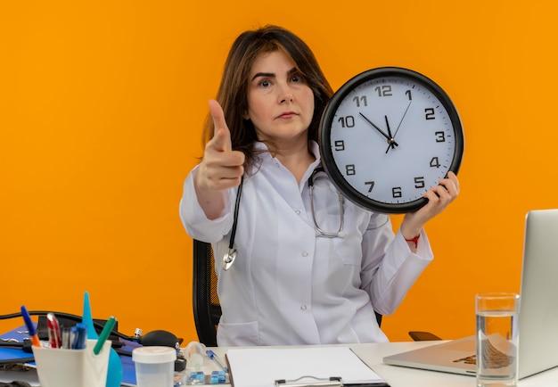 Médica de meia-idade confiante usando túnica médica e estetoscópio sentada na mesa com a área de transferência de ferramentas médicas e laptop segurando o relógio apontando isolado
