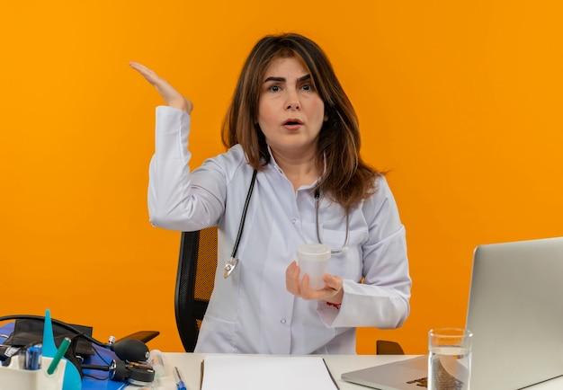 Médica de meia-idade confusa, vestindo bata médica e estetoscópio, sentada à mesa com a área de transferência de ferramentas médicas e laptop segurando um copo médico, mostrando a mão vazia