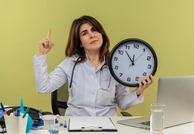 Médica de meia-idade descontente, vestindo bata médica e estetoscópio, sentada à mesa com ferramentas médicas e laptop segurando o relógio apontando para cima isolado