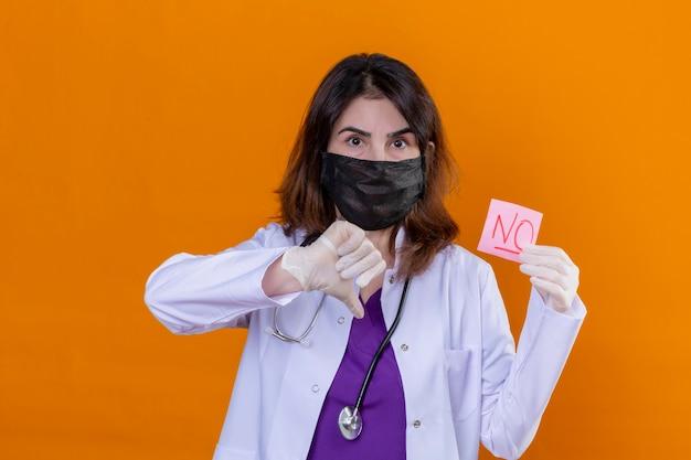Médica de meia-idade descontente, vestindo jaleco branco com máscara facial protetora preta e com um estetoscópio segurando um papel lembrete com a palavra sem mostrar o polegar