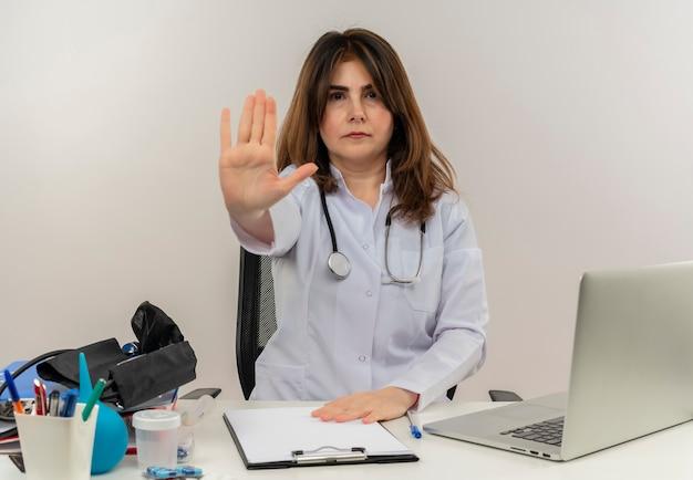 Médica de meia-idade estrita vestindo túnica médica com estetoscópio sentada na mesa de trabalho no laptop com ferramentas médicas mostrando gesto de parada em backgroung branco isolado com espaço de cópia