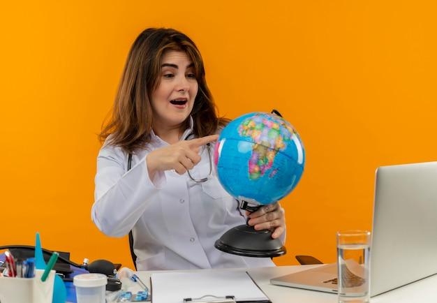 Médica de meia-idade impressionada usando túnica médica com estetoscópio sentada na mesa de trabalho no laptop com ferramentas médicas segurando e colocando o dedo no globo na parede laranja com espaço de cópia