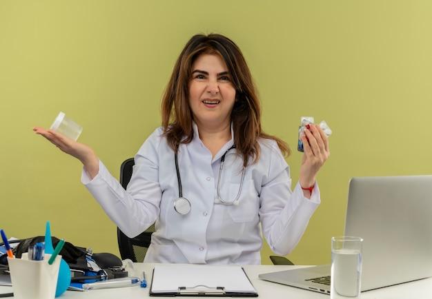 Médica de meia-idade irritada, vestindo túnica médica e estetoscópio, sentada à mesa com ferramentas médicas e um laptop segurando medicamentos e o copo isolados
