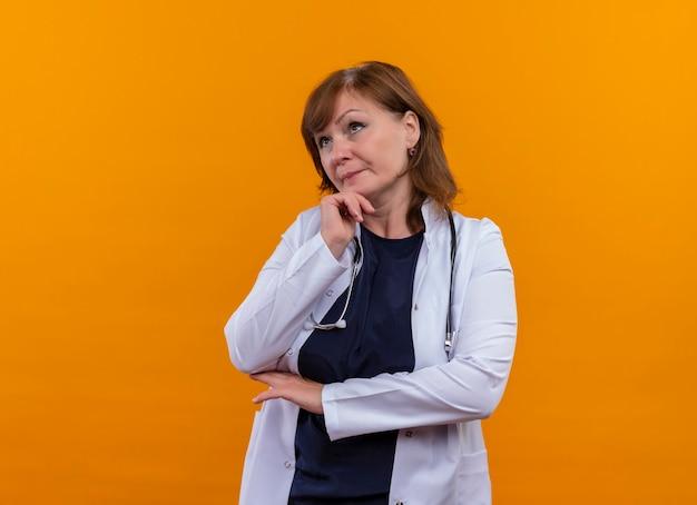 Médica de meia-idade pensativa, vestindo túnica médica e estetoscópio, colocando mão no queixo na parede laranja isolada com espaço de cópia