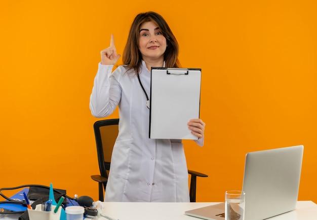 Médica de meia-idade satisfeita vestindo túnica médica com estetoscópio sentada na mesa de trabalho no laptop com ferramentas médicas segurando a prancheta e aponta para cima na parede laranja com espaço de cópia