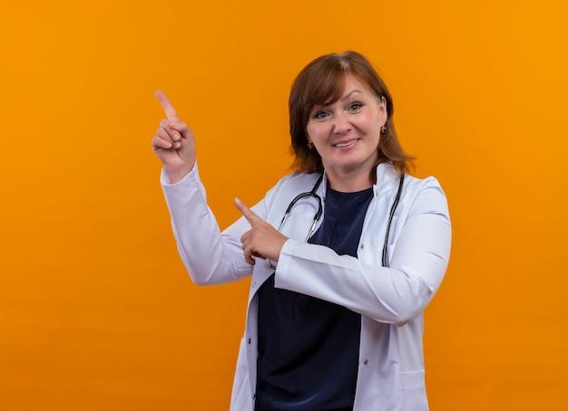 Médica de meia-idade sorridente usando roupão médico e estetoscópio apontando com os dedos para cima na parede laranja isolada com espaço de cópia