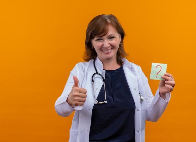 Médica de meia-idade sorridente usando túnica médica e estetoscópio mostrando o polegar e segurando uma nota de papel com ponto de interrogação na parede laranja isolada com espaço de cópia