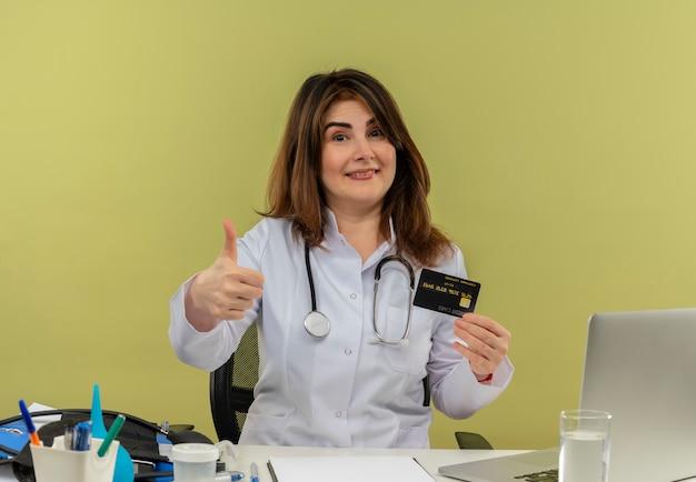 Médica de meia-idade sorridente, usando túnica médica e estetoscópio, sentada à mesa com ferramentas médicas e um laptop segurando um cartão de crédito, mostrando o polegar isolado