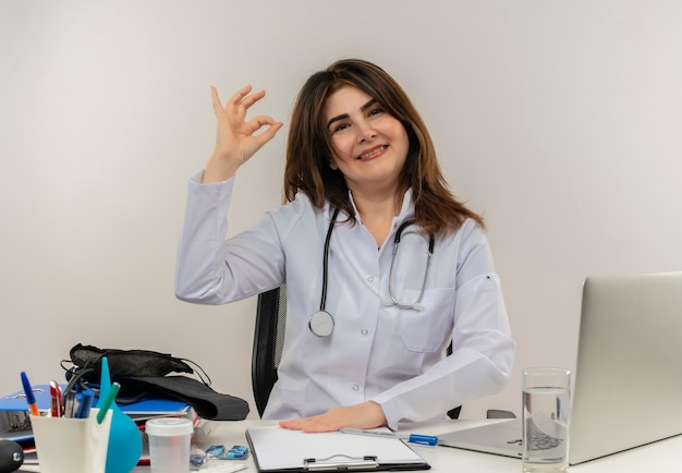 Médica de meia-idade sorridente, vestindo túnica médica, com estetoscópio sentada na mesa de trabalho no laptop com ferramentas médicas, mostrando um gesto certo em um backgroung branco isolado com espaço de cópia