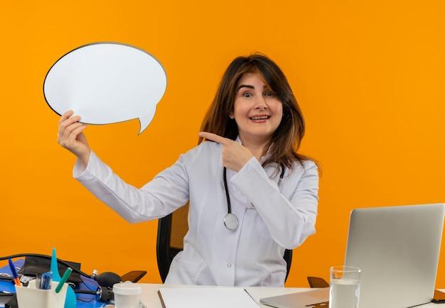 Médica de meia-idade sorridente, vestindo túnica médica com estetoscópio, sentada na mesa de trabalho no laptop, segurando ferramentas médicas e apontando para uma bolha de bate-papo na parede laranja