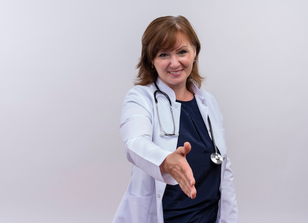 Médica de meia-idade sorridente, vestindo túnica médica e estetoscópio, fazendo um gesto de aperto de mão na parede branca isolada com espaço de cópia