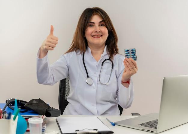 Médica de meia-idade sorridente, vestindo um manto médico com estetoscópio, sentada na mesa de trabalho no laptop com ferramentas médicas, segurando o cartão de crédito com o polegar na parede branca